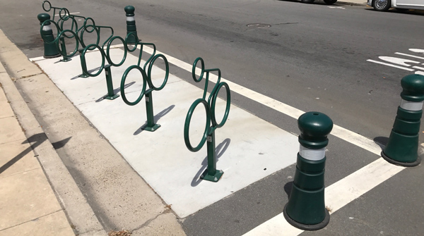 Bollards are a more secure, but more permanent, solution to delineating a bicycle corral.