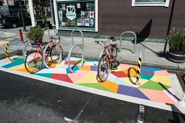 On-street bicycle parking that has been painted with bright colors and is highly visible.